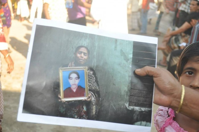 Mother holding the image of her only daughter who died in the Tazreen factory fire in Nischintapur (photograph by Mahmudul Sumon, 22 November 2013).